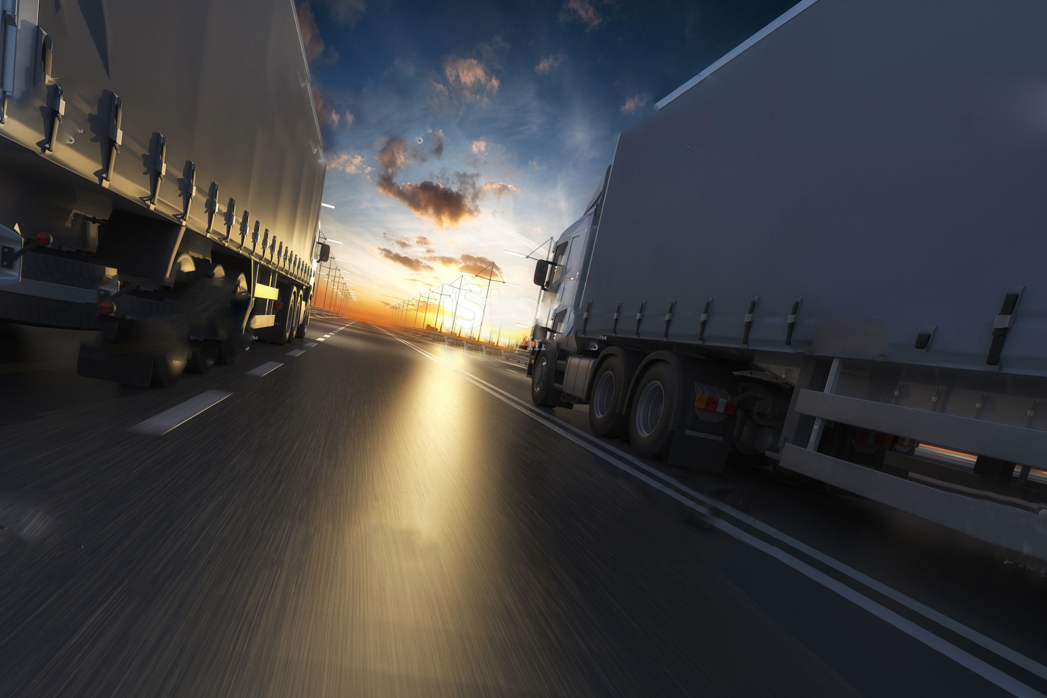 Two HGV trucks driving side by side into the sunset