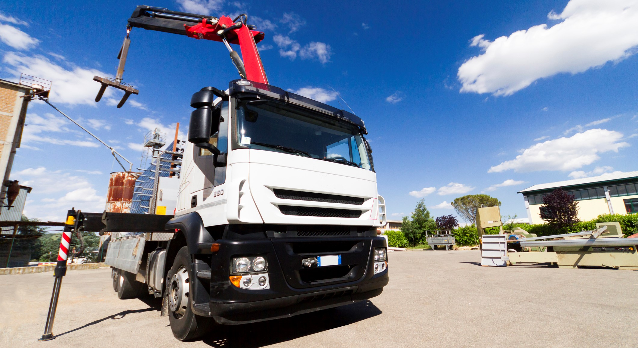 A white HIAB crane loaded lorry unloading pallets in a yard