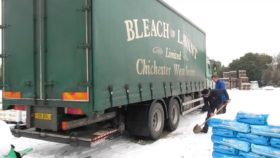 An HGV stuck in the snow with two men attempting to dig it out