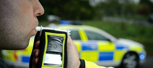man blowing into a breathalyser held by a police officer